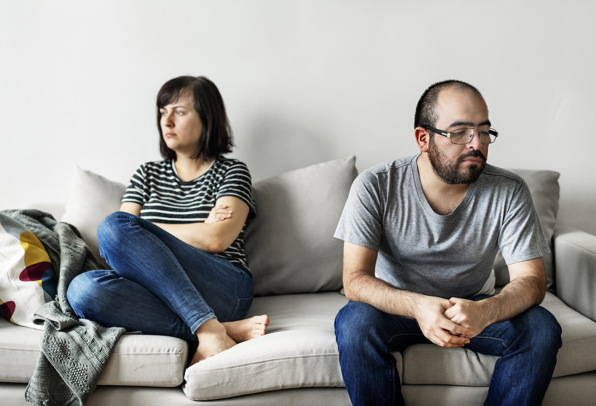 Unhappy couple arguing on the sofa